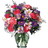 Gorgeous selection of Purple and Pink Flowers adorned in a Glass Vase
