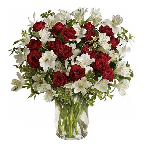 Ravishing Red N White Mixed Florals decked in a Glass Vase